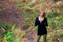 美丽的神奇女孩在秋天森林里 免版税库存照片