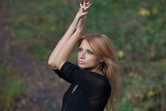美丽的神奇白肤金发的妇女在秋天森林里 免版税库存照片