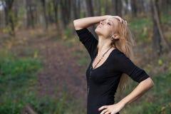 美丽的神奇白肤金发的妇女在秋天森林里 免版税图库摄影