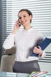 美丽的秘书谈话在电话 免版税库存图片
