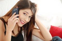 美丽的移动电话告诉的妇女年轻人 免版税库存照片