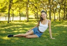 美丽的稀薄的女孩坐草 免版税库存图片