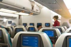 美丽的空中小姐或战斗乘务员等待的服务乘客在船上内部飞机的 库存图片