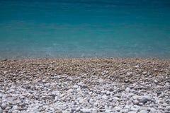 美丽的空的海滩小卵石用绿松石纯净的清楚的水与拷贝的夏令时间隔背景旅游目的地, olud 图库摄影