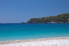 美丽的空的海滩用在oludeniz的绿松石水与拷贝空间背景旅游目的地, oludeniz, t的夏令时 免版税库存照片