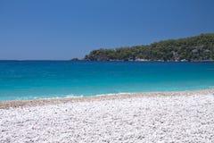 美丽的空的海滩用在oludeniz的绿松石水与拷贝空间背景旅游目的地, oludeniz, t的夏令时 库存照片