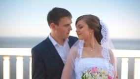 美丽的站立在阳台的新娘和新郎俯视海 股票视频