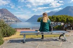 美丽的端庄的妇女坐公园长椅和看湖卢加诺的和阿尔卑斯山在瑞士 库存照片
