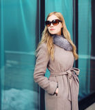 美丽的端庄的妇女穿戴了外套和太阳镜户外 库存图片