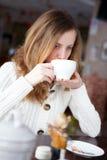 年轻美丽的端庄的妇女饮用的咖啡或茶 库存照片