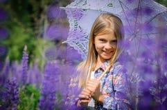 美丽的笑的女孩在紫色领域 免版税库存图片
