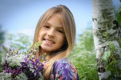 美丽的笑的女孩在紫色领域 库存照片