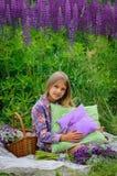 美丽的笑的女孩在紫色领域 库存图片