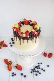 美丽的米黄色的蛋糕装饰用草莓,蓝莓,巧克力,蛋白杏仁饼干,站立在白色木桌上 免版税库存照片