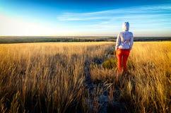 年轻美丽的精瘦的女孩穿红色裤子,并且白色有冠乌鸦在金黄草中的一个领域停留在日落,回到照相机 免版税库存照片