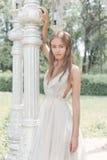 美丽的精美一套轻的米黄婚礼礼服的新娘性感的女孩在庭院明亮的晴朗的温暖的天走 免版税图库摄影