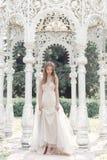 美丽的精美一套轻的米黄婚礼礼服的新娘性感的女孩在庭院明亮的晴朗的温暖的天走 图库摄影