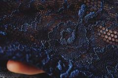 美丽的精美透雕细工深蓝鞋带在手中 免版税库存照片