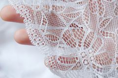 美丽的精美透雕细工白色鞋带在手中 免版税库存图片