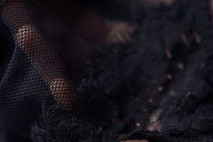 美丽的精美透雕细工黑鞋带在手中 免版税库存照片