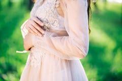 美丽的精美鞋带婚礼礼服,手工制造,缝合的样式,逗人喜爱的女孩美好的形状,特写镜头,新娘,手,腰部, 免版税库存图片