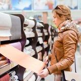 美丽的繁忙的妇女在选择墙纸画象图象的DIY超级市场 免版税图库摄影