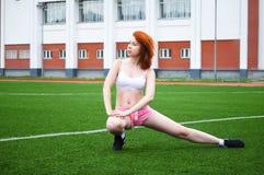 美丽的红发女孩向体育求助和做锻炼在体育场 免版税图库摄影