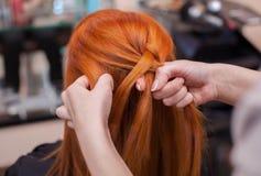 美丽的红发女孩,美发师织法法国辫子特写镜头 库存照片