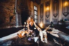 年轻美丽的红发女孩画象一个哥特式巫婆的图象的在万圣夜 免版税图库摄影