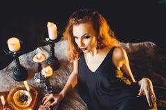年轻美丽的红发女孩画象一个哥特式巫婆的图象的在万圣夜 免版税库存图片