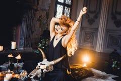 年轻美丽的红发女孩画象一个哥特式巫婆的图象的在万圣夜 免版税库存照片