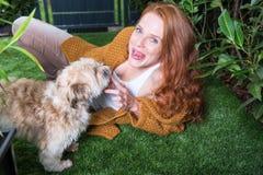 美丽的红发妇女使用与她的狗在庭院里 免版税库存图片