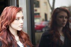 美丽的红发妇女和反映 免版税库存照片