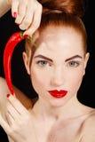 美丽的红发妇女画象用炽热辣卡宴辣椒 库存图片