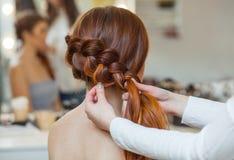 美丽的红发长毛的女孩,美发师编织法国辫子,在美容院的特写镜头 免版税库存照片