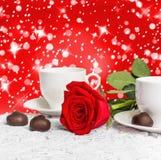 美丽的红色玫瑰和杯子热的茶用巧克力 免版税库存照片