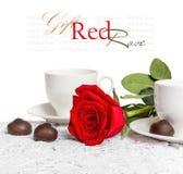 美丽的红色玫瑰和杯子热的茶用巧克力 免版税图库摄影
