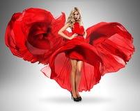 美丽的红色礼服的热的白肤金发的妇女 免版税库存图片