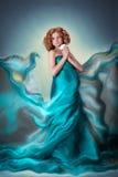美丽的红色蓝色飞行透明硬沙织品礼服的头发怀孕的嫩妇女有花的 免版税库存图片