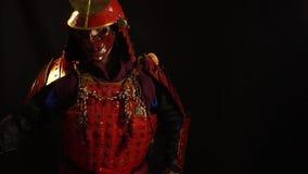 美丽的红色装甲和邪魔的一个红色防御面具的一个武士人从鞘里面拉katana并且举行 股票视频