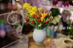 美丽的红色郁金香和黄色含羞草在一个蓝色花瓶 图库摄影