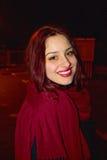 美丽的红色顶头女孩顶头射击有完善的微笑、俏丽的眼睛和面孔的和有红色围巾的在冷的冬天夜 库存图片