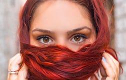 美丽的红色顶头女孩顶头射击有完善的神色的,俏丽的眼睛和在手边敲响 免版税库存图片