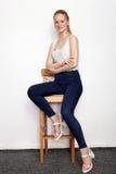 年轻美丽的红头发人初学者模型妇女全长画象实践摆在的白色T恤杉蓝色牛仔裤的显示情感 库存图片