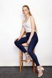 年轻美丽的红头发人初学者模型妇女全长画象实践摆在的白色T恤杉蓝色牛仔裤的显示情感 图库摄影