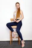 年轻美丽的红头发人初学者模型妇女全长画象实践摆在的白色T恤杉蓝色牛仔裤的显示情感 免版税库存图片