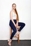 年轻美丽的红头发人初学者模型妇女全长画象实践摆在的白色T恤杉蓝色牛仔裤的显示情感 免版税图库摄影