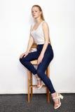 年轻美丽的红头发人初学者模型妇女全长画象实践摆在的白色T恤杉蓝色牛仔裤的显示情感 库存照片