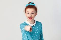 美丽的红头发人女孩,佩带的蓝色礼服,打开的嘴广泛,惊奇冲击了神色,把手指指向照相机 免版税库存图片