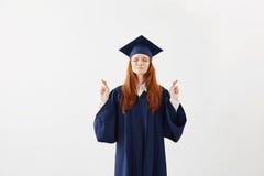 美丽的红头发人女性毕业生祈祷在白色背景 复制空间 免版税库存照片